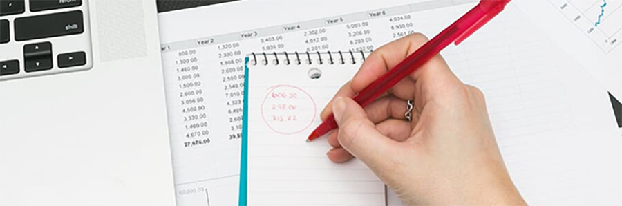 Woman's hand writing figures in a notepad with a red pen.