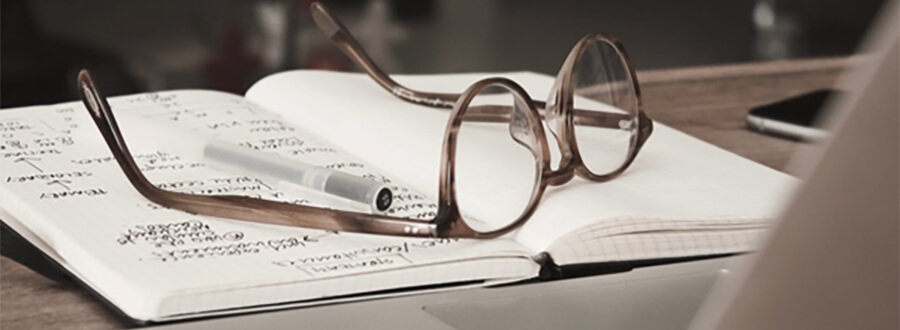 Glasses and pen on an open notebook.
