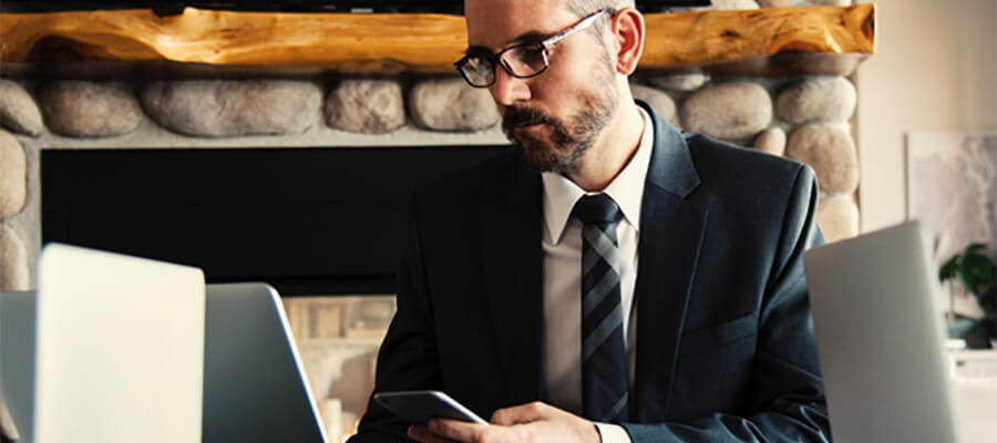 Man in suit using laptop and phone.