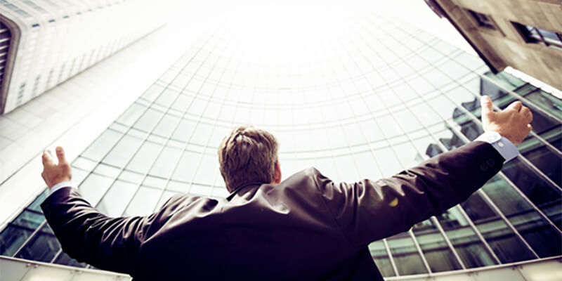 Businessman looking up at a skyscraper with his arms open wide.