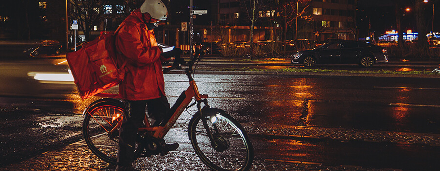 Bike courier on a wet night in the city.