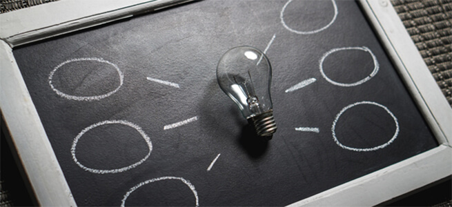Lightbulb on a blackboard with spaces for ideas.