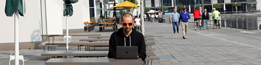 Man using a laptop in a foreign location.