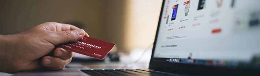 Male hand holding a credit card over a laptop.