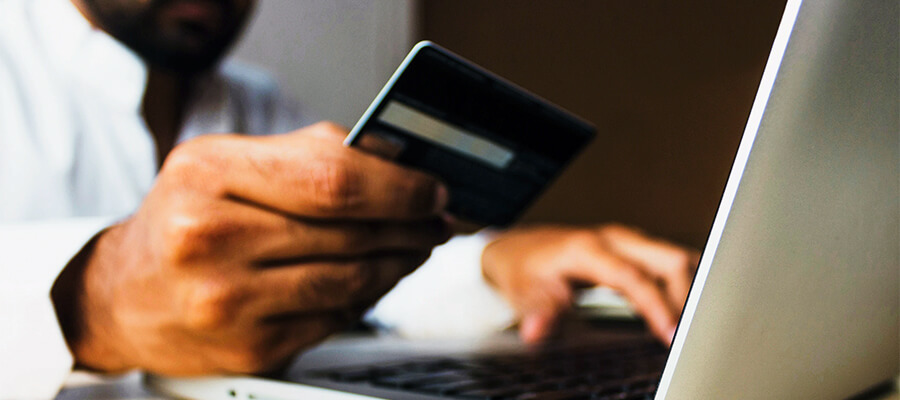 Man using a credit card to buy a product online.
