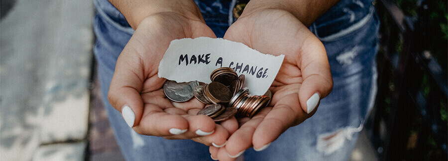 Woman's hands holding loose change with the caption - 'Make a Change'