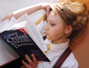 A girl reading the Oxford English Dictionary.