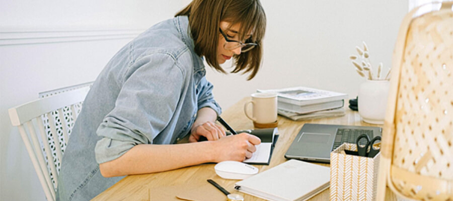 Woman writing in a notebook. Working at home.