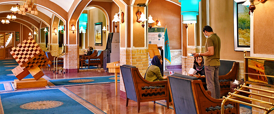 Lobby of a 5 star hotel with member of staff helping guests.