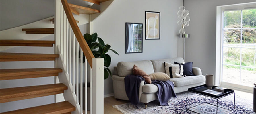 House interior with sweeping staircase and sofa.