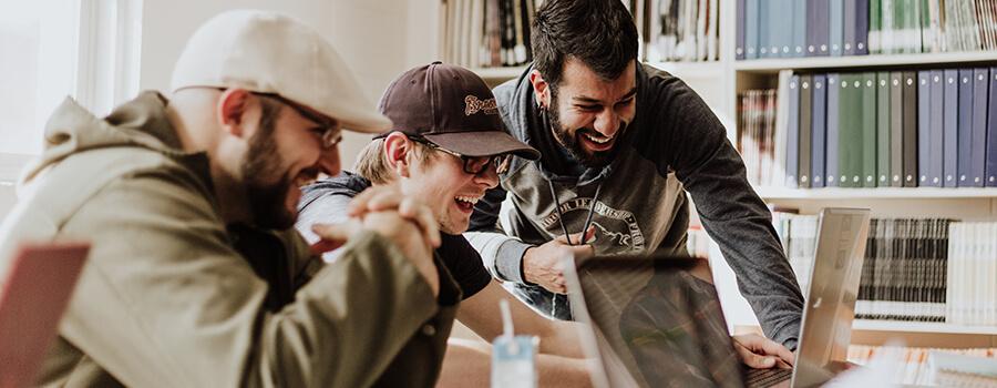 Three men laughing at something on a laptop.