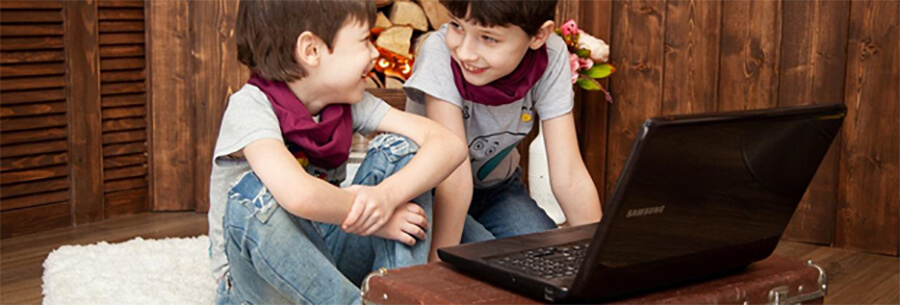 Two young children with a laptop.