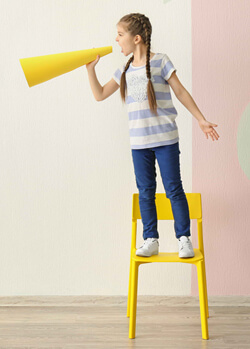 Child standing on a chair talking into a megaphone.