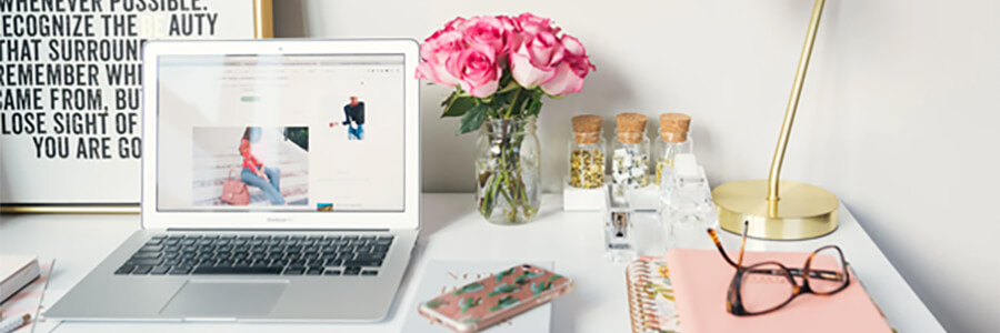 Desk with laptop, flowers, poster and glasses.