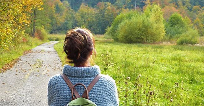 A girl in a sweater setting out on a journey down a country road, representing the idea to move away and start over.