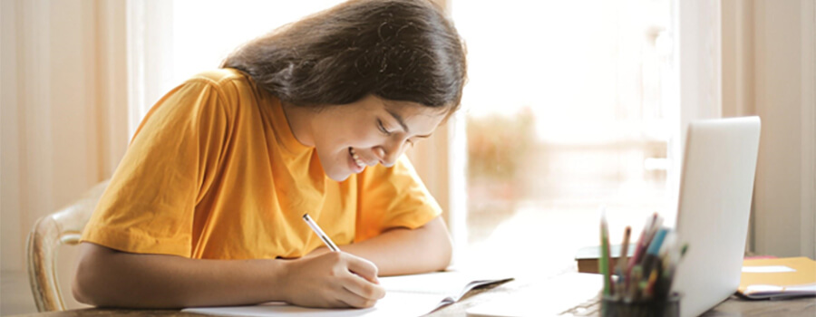 Student with a yellow tee-shirt studies online.