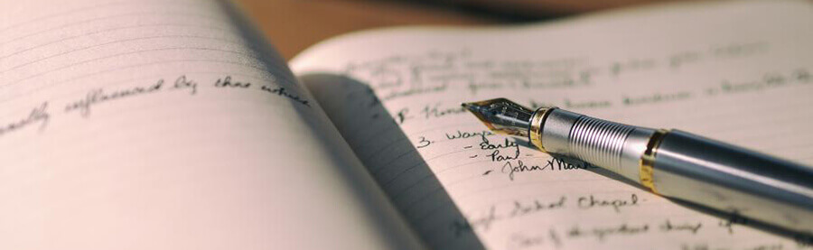 Fountain pen on open notebook with handwriting.