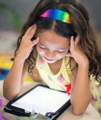 Girl child looking at a tablet.