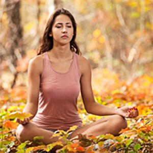 Woman meditating in a forest