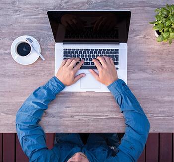 Ręce mężczyzny, wpisując na laptopie.