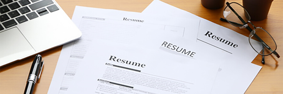 Copies of a resume with laptop, pen and glasses.