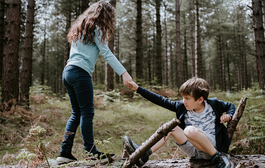 Girl helping a boy up after a fall in a forest.