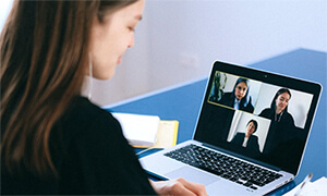 Woman communicating via Zoom on a laptop.