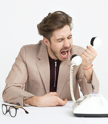 Man shouting down a landline phone.