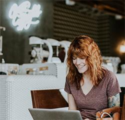 Smiling woman on laptop.