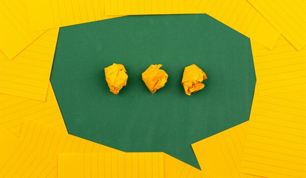 A speech bubble made from green and yellow paper.