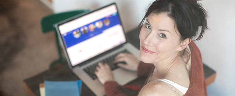 Smiling woman looking up from her laptop.