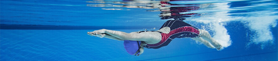 Swimmer underwater in a pool.
