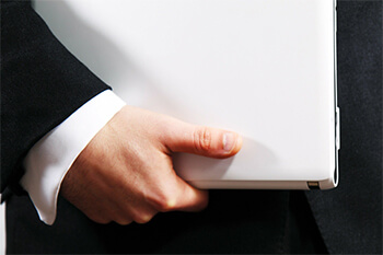 Man in suit carrying a laptop.