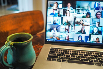Laptop showing video conference calling software.