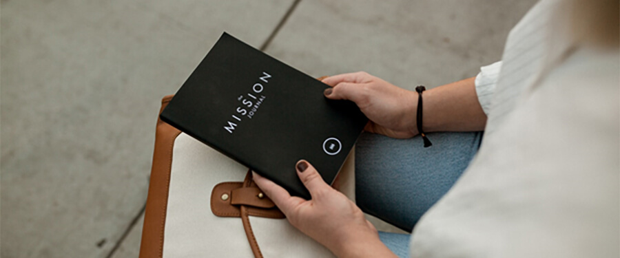 Woman with book called 'Mission'