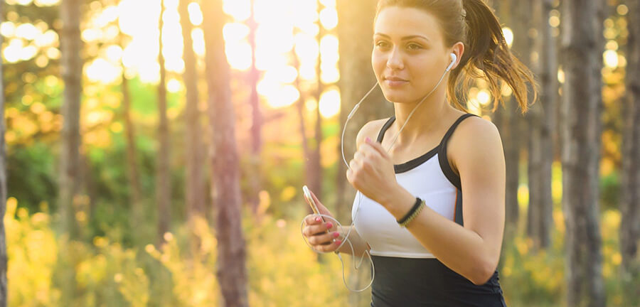 Woman jogging in the woods with headphones.