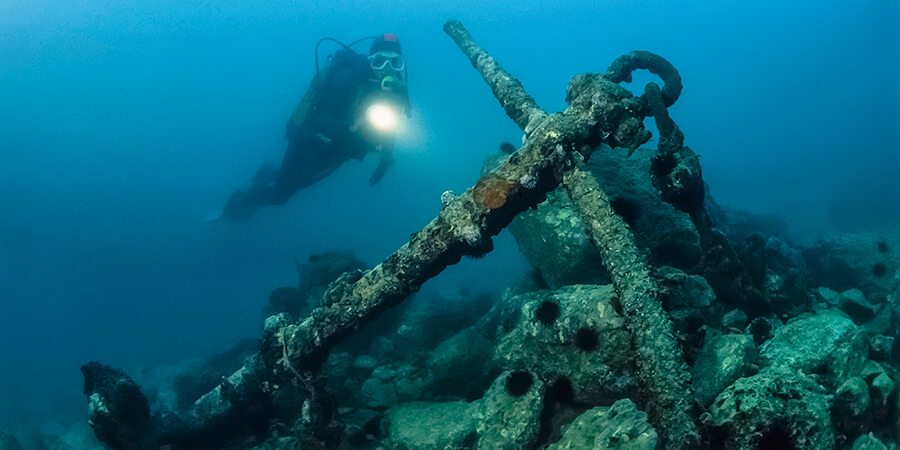 Wreck diver approaching old anchor.